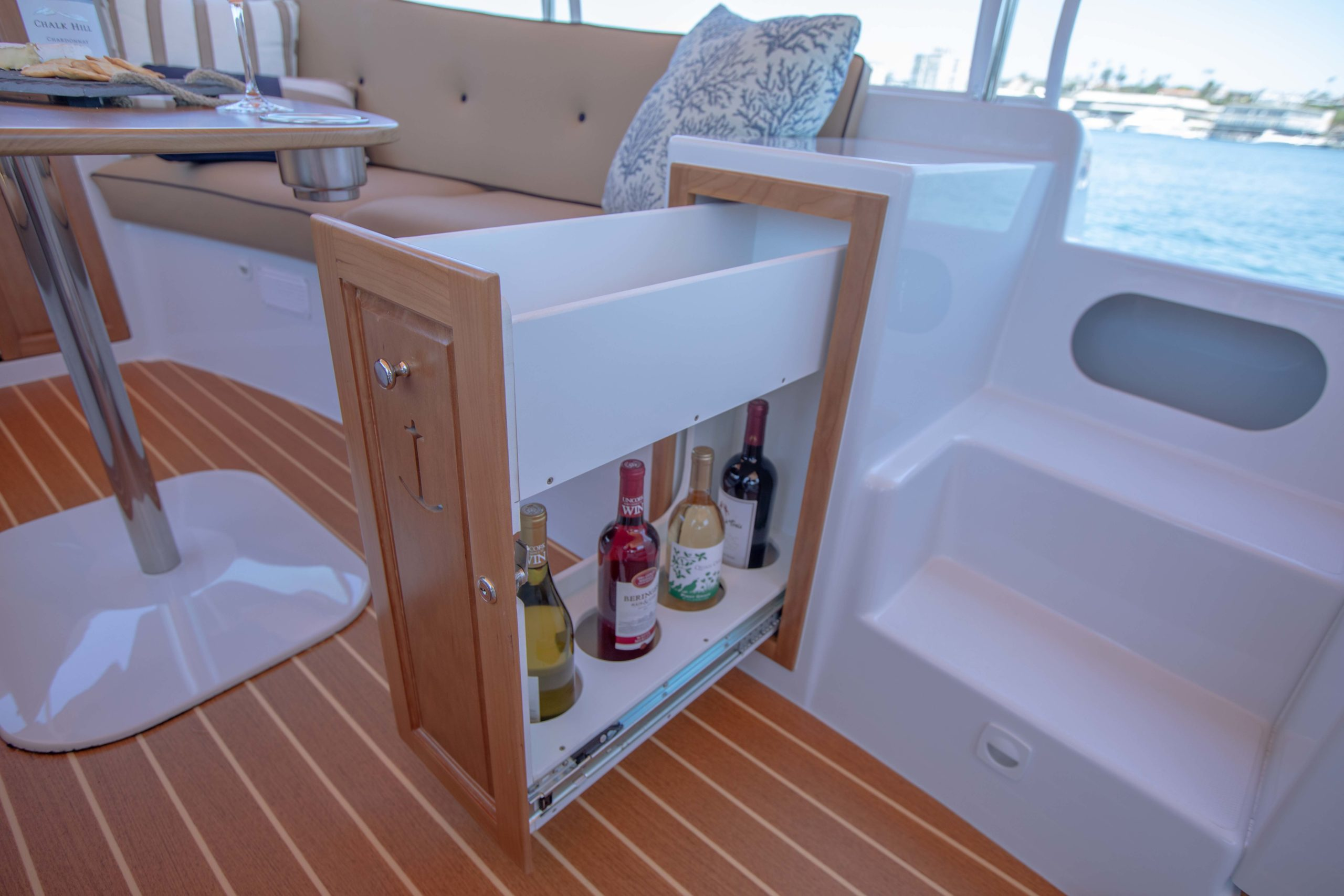 Photo of Duffy Electric Boats 22 foot Cuddy Cabin interior, showing the wine drawer open stocked with wine and other items in the top space.